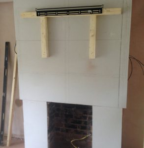 hidden TV cables, tv mounting in progress on grey plasterboard above open fireplace