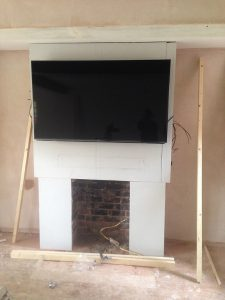 wall mounted tv , black tv on grey plaster board wall