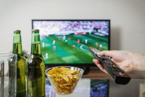 wall mounted tv with two beer bottles and a bowl of crisps