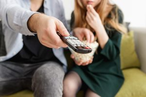 tv couple holding a remote and popcorn